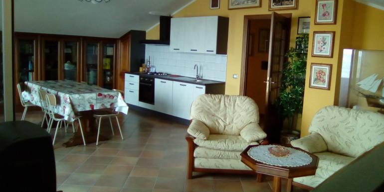 ampio salone con cucina e divano e poltrone